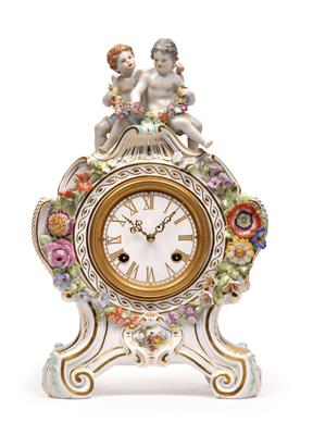 A porcelain clockcase with movement, with two amorettes, - Glass and Porcelain